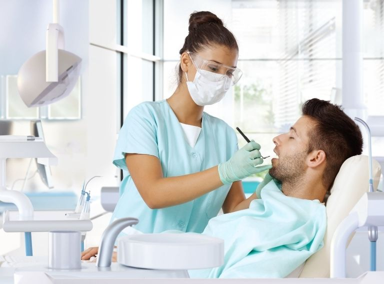 Bác sĩ tiến hành vệ sinh răng miệng chuẩn bị cho bước trồng răng